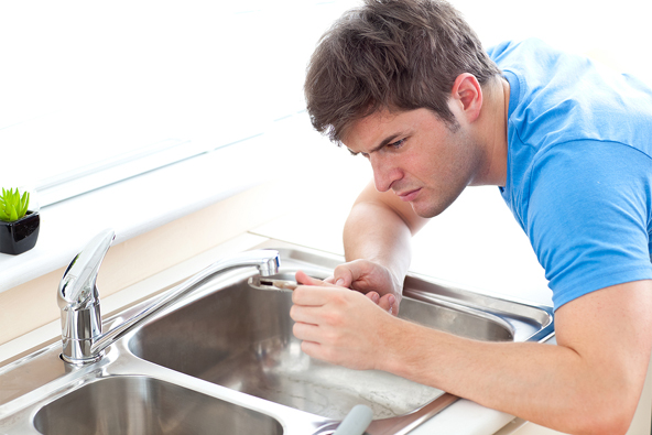 Concentrated Man Repairing His Sink In The Kitchen